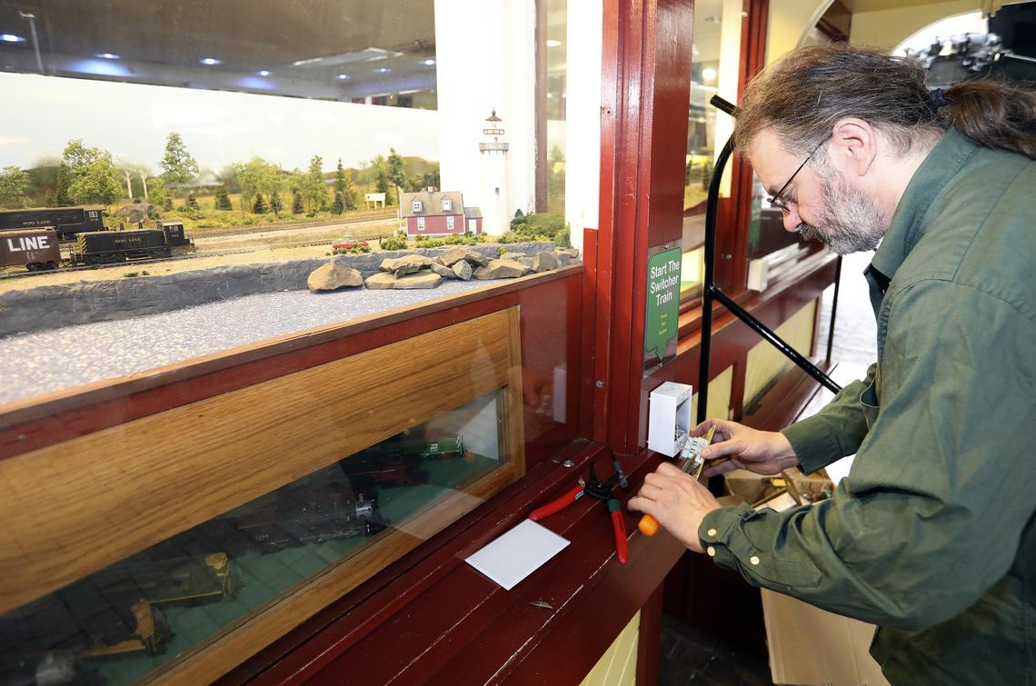 Martin Dean of Duluth AV Logistics works on a new motion detector in the Lake Superior Railroad Museum Monday. The museum replaced touch buttons on its exhibits with the touchless detectors. (Steve Kuchera / skuchera@duluthnews.com)