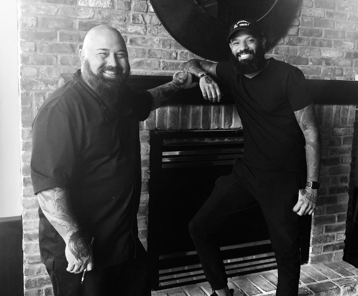 A smiling Brian Ingram and Justin Sutherland lean on a fireplace upstairs at The Gnome. Ingram is bald, bearded, and white. Sutherland is wearing his ever-present In Diversity We Trust baseball hat, clad in all black, and Black