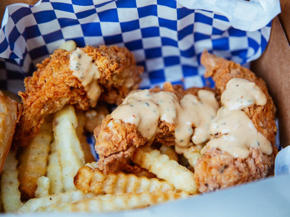 A box with white and blue checked paper filled with chicken fingers, covered in a creamy sauce, over crinkle cut fries