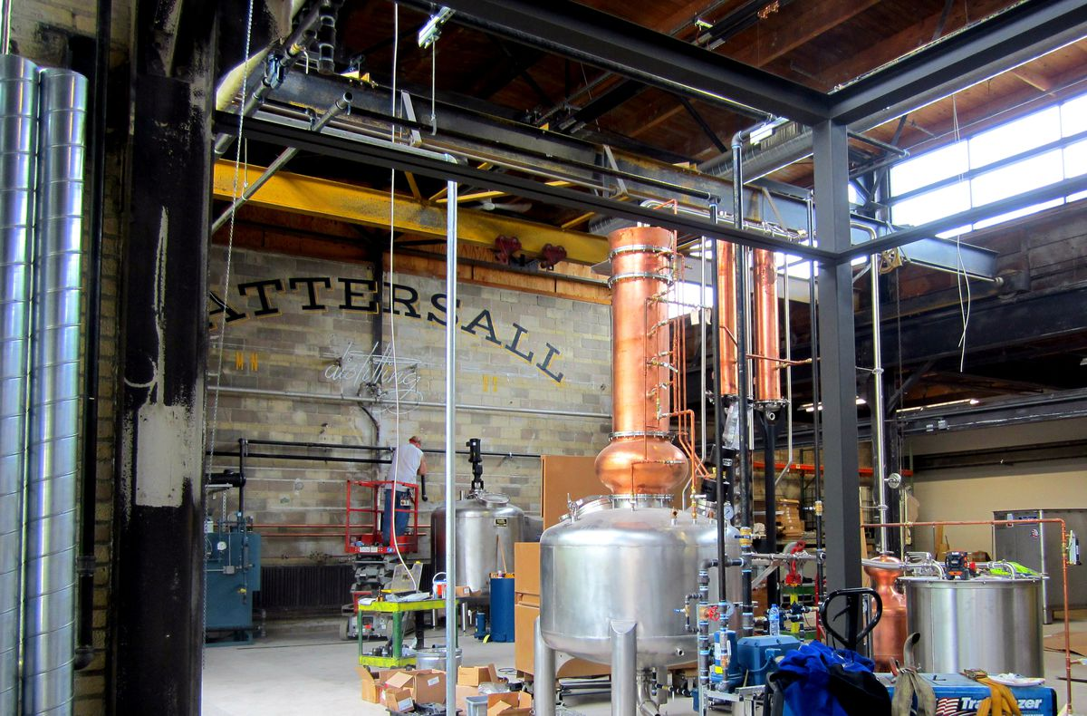 A copper topped distillery tank in front of a wood wall with the Tattersall painted in an arch across it