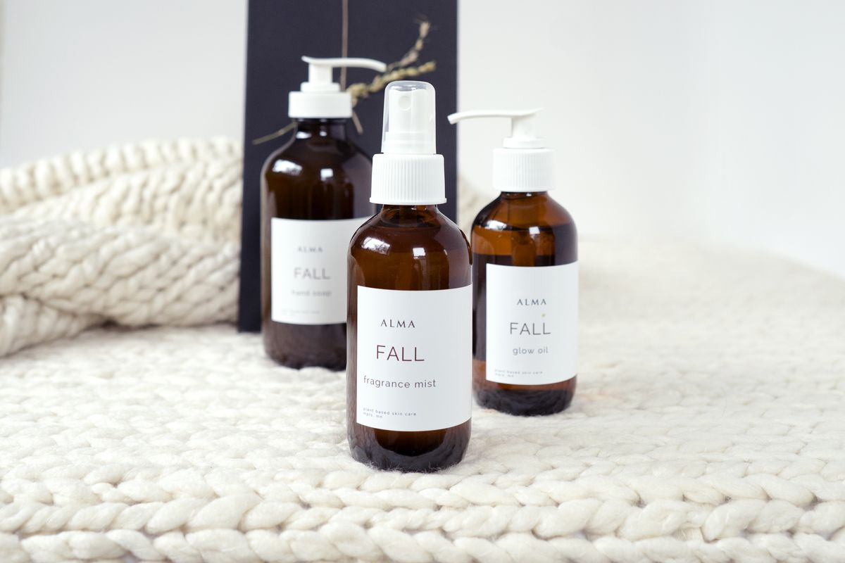 Four brown glass bottles with clean white labels in a fine line font that reads Alma, on a white background on top of a white chunky knit blanket