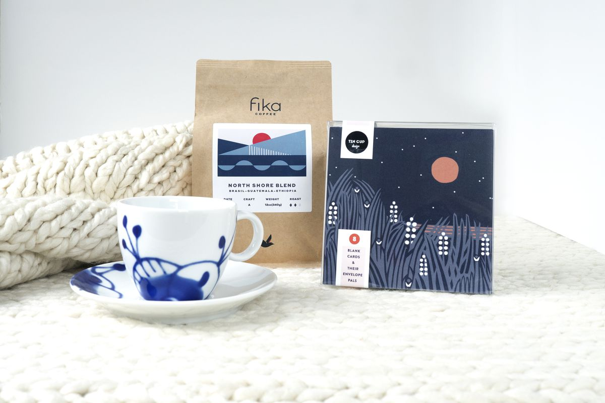 A white and blue tea cup in front of a bag of Fika coffee in a brown bag with Scandinavian designed label of blue and gray blue geometric shapes. A package of notecards are deep navy with white and gray wild rice stalks in front of a red harvest moon
