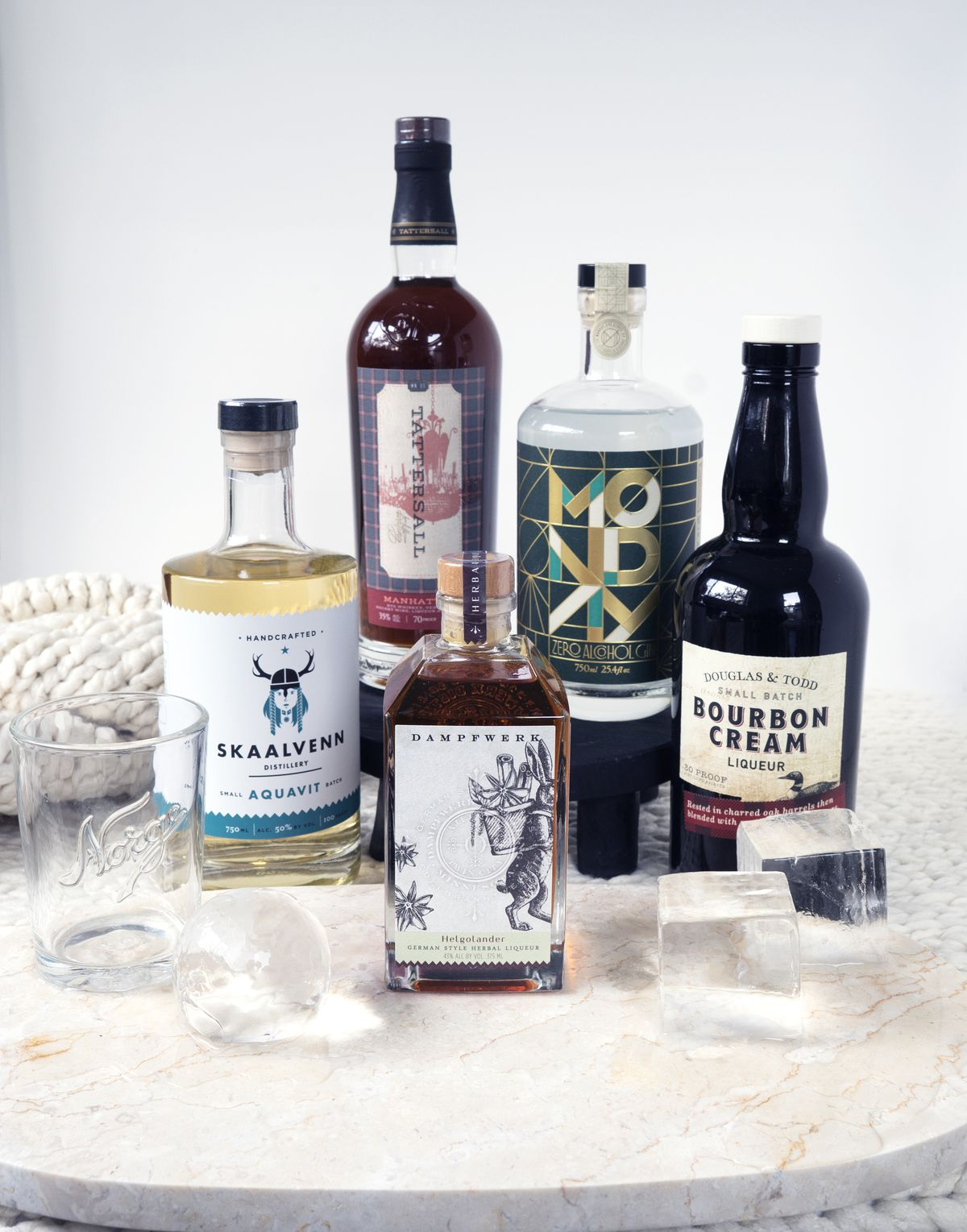 A selection of local liquor bottles, listed in the text, with two large glasses and crystal clear ice cubes