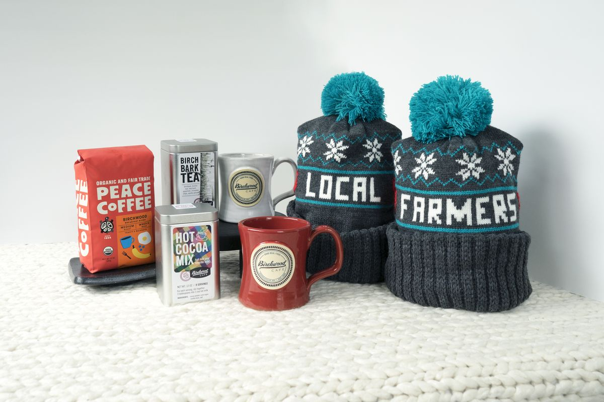 Two hats with pom poms, two handmade pottery coffee mugs, Peace's Birchwood blend coffee, a tin of birchbark tea and a hot cocoa set