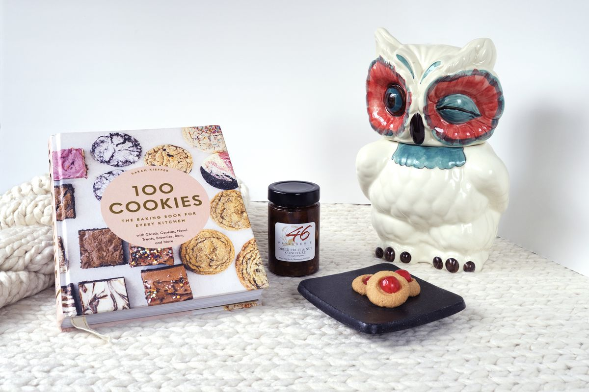 Sarah Kieffer's 100 Cookies cookbook, a jar of nut spread and a large owl cookie jar on a white background