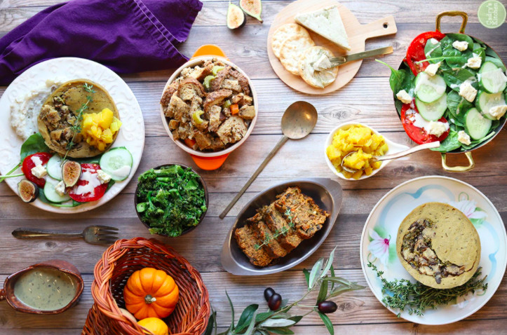 A table is set with sides and salads with pumpkins in a cornucopia and purple cloth napkins. There's a sliced loaf, cucumber salad, and stuffing