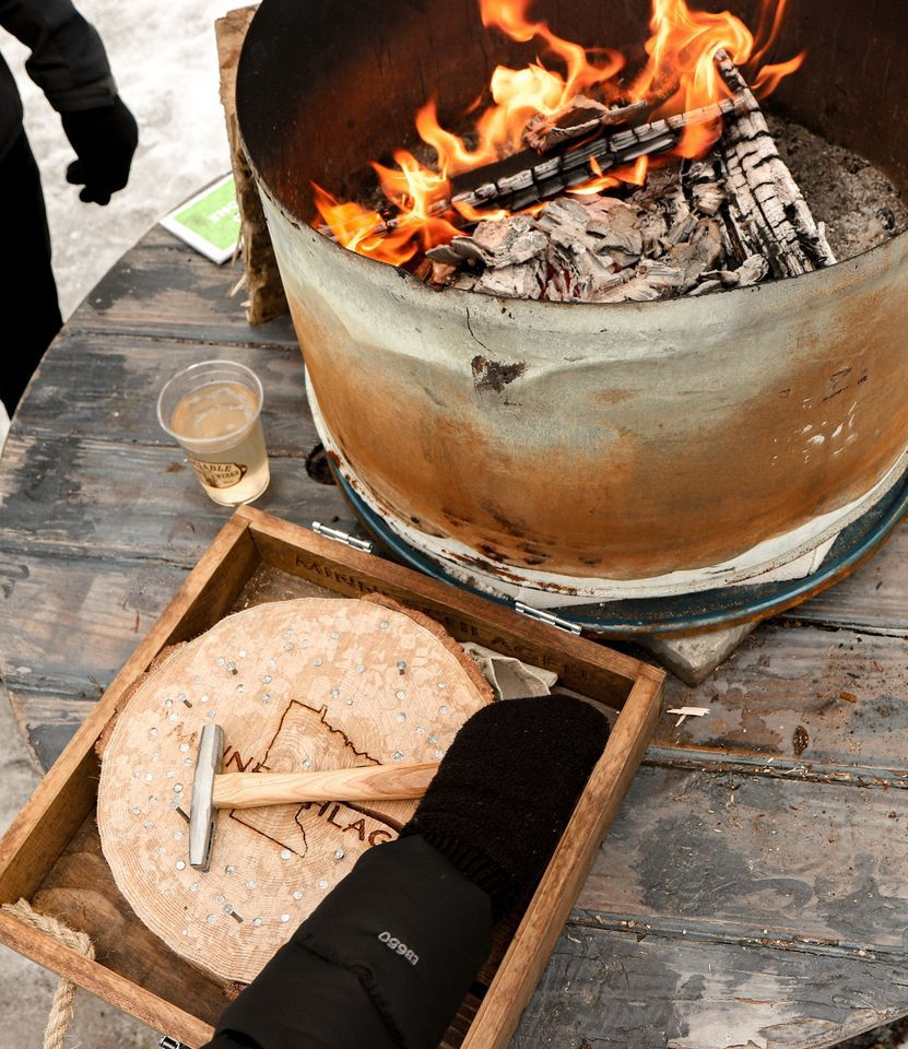 A small outdoor firepit with a cup of cider for guests of the cidery.