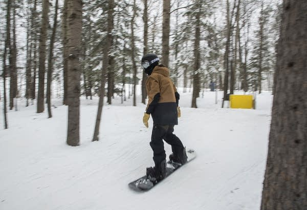 A person snowboards through trees.