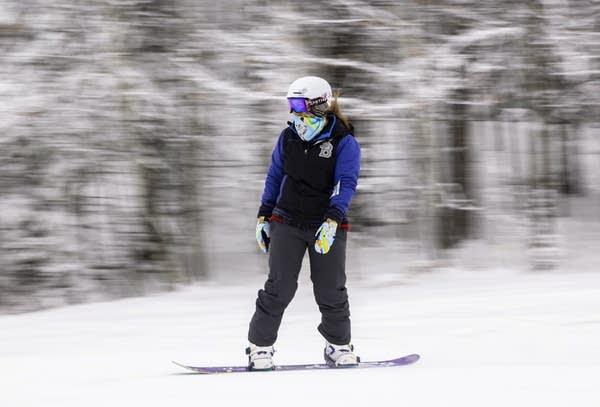 A person snow boards down a slope