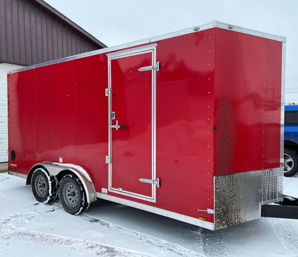 A red trailer with a large door parked in a snowy driveway