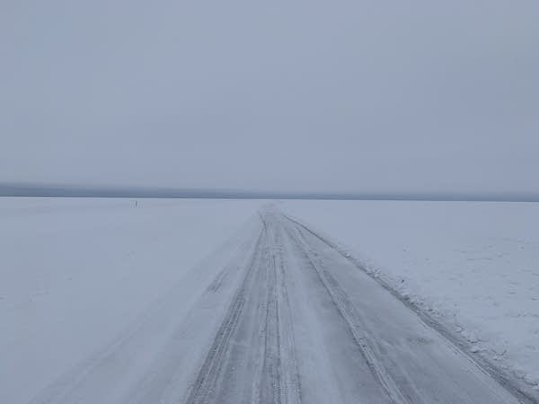 A road on a frozen lake fades into the distance.