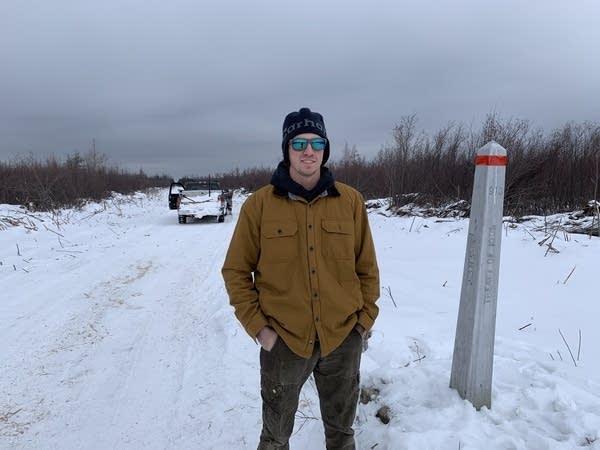 A man stands next to a metal pole.