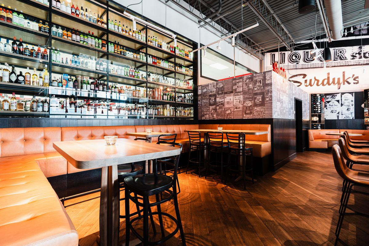 A buff leather booth stretches around a corner and along the back wall beneath glass shelves of booze
