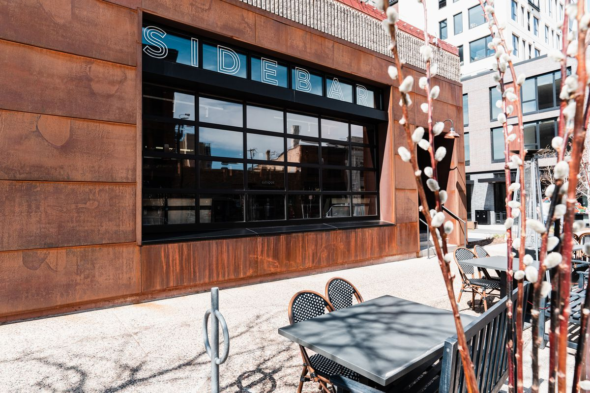 The copper exterior of the restaurant is dominated by a black silloutted garage door front window space that occupies much of the facade. It's all visible past sidewalk tables decorated with pussy willows.