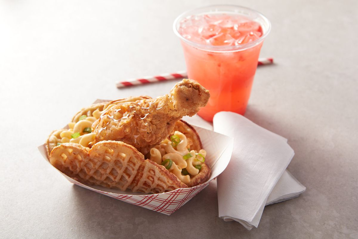 A red and white paper boat buckles under the weight of a folded waffle filled with mac and cheese, garnished with a jaunty little chicken drummy