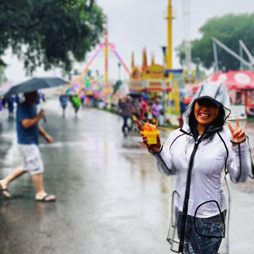 A woman in a rain jacket hold a cup of shaved ice on a rainy day. Brightly colored fair vendors are visitble in the background, lit up