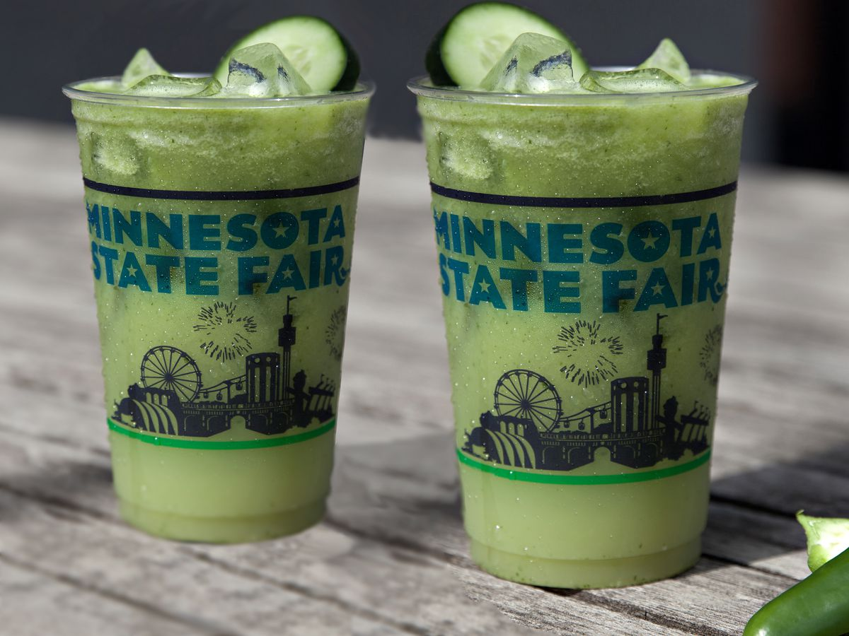 Two State Fair branded plastic cups are filled with ice and a light green liquid, garnished with a cucumber slice