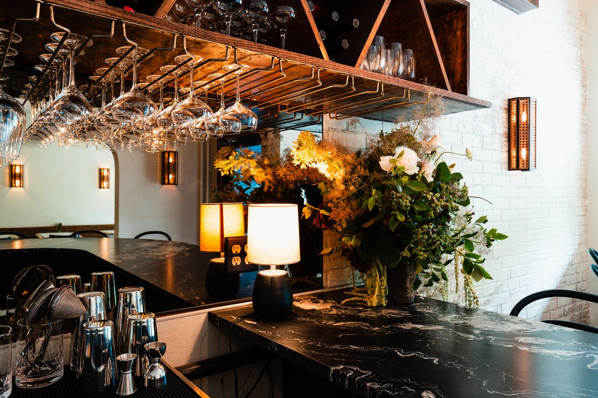A stone countertop is adorned with a large bouquet of greenery and white roses. Overhead is a rack for hanging glasses