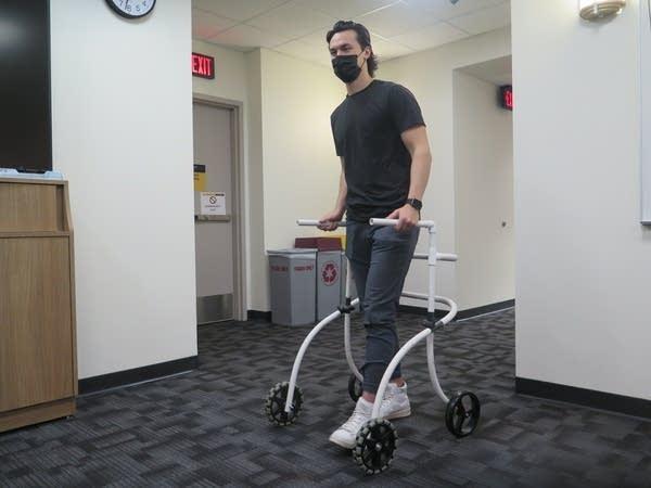 A man walks with a walker